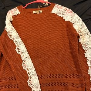 Burnt orange sweater with detail on sleeves